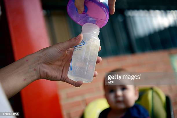 A woman prepares a milk bottle to feed her baby in Caracas on June 18 2013 The congress would debate about the use of feeding bottle trying to...