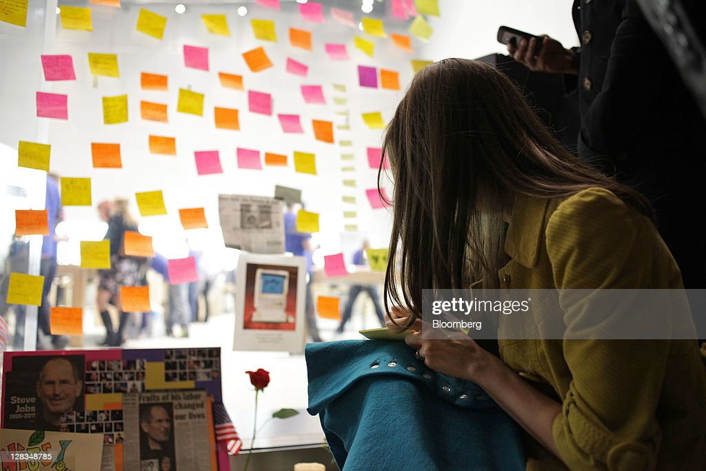 A woman prepares a Post-it note at a memorial for Steve Jobs, co-founder and former chief executive officer of Apple Inc., outside an Apple store in New York, U.S., on Thursday, Oct. 6, 2011. Jobs, who built the world's most valuable technology company by creating devices that changed how people use electronics and revolutionized the computer, music and mobile-phone industries, died on Oct. 5. He was 56. Photographer: Stephen Yang/Bloomberg via Getty Images