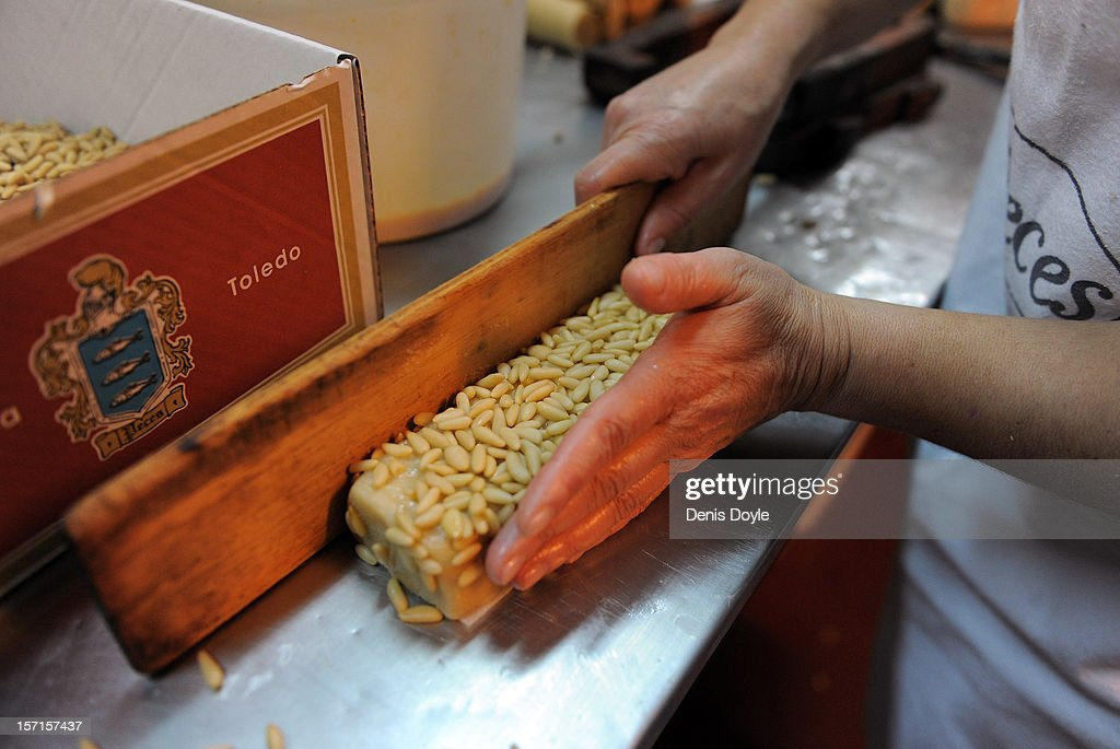 A woman prepares a traditional 'Barra de pinones' cake at the at the Peces Mazapanes bakery on November 28, 2012 in the town of Consuegra, near Toledo, Spain. The company opens annually during the three months leading up to christmas hiring 32 workers to produce traditional Spanish christmas cakes called Mazapanes.