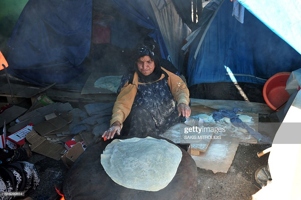 A woman prepares bread at a makeshift camp set near a gas station some 20 km from the Greek-Macedonian border, on 25 May, 2016 in Polykastro. In an operation which began shortly after sunrise on May 24, hundreds of Greek police began evacuating the sprawling camp which is currently home to 8,400 refugees and migrants, among them many families with children, an AFP correspondent said. At its height, there were more than 12,000 people crammed into the site, many of them fleeing war, persecution and poverty in the Middle East and Asia, with the camp exploding in size since Balkan states began closing their borders in mid February in a bid to stem the human tide seeking passage to northern Europe. / AFP / SAKIS
