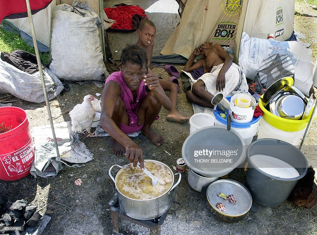 A woman prepares food by a tent in a makeshift camp on October 17, 2008 in the village of Cabaret, 35km north of Port-au-Prince, where some 700 people, mostly women and girls, have taken refuge after their homes were destroyed by hurricane Ike in September. AFP PHOTO/Thony BELIZAIRE
