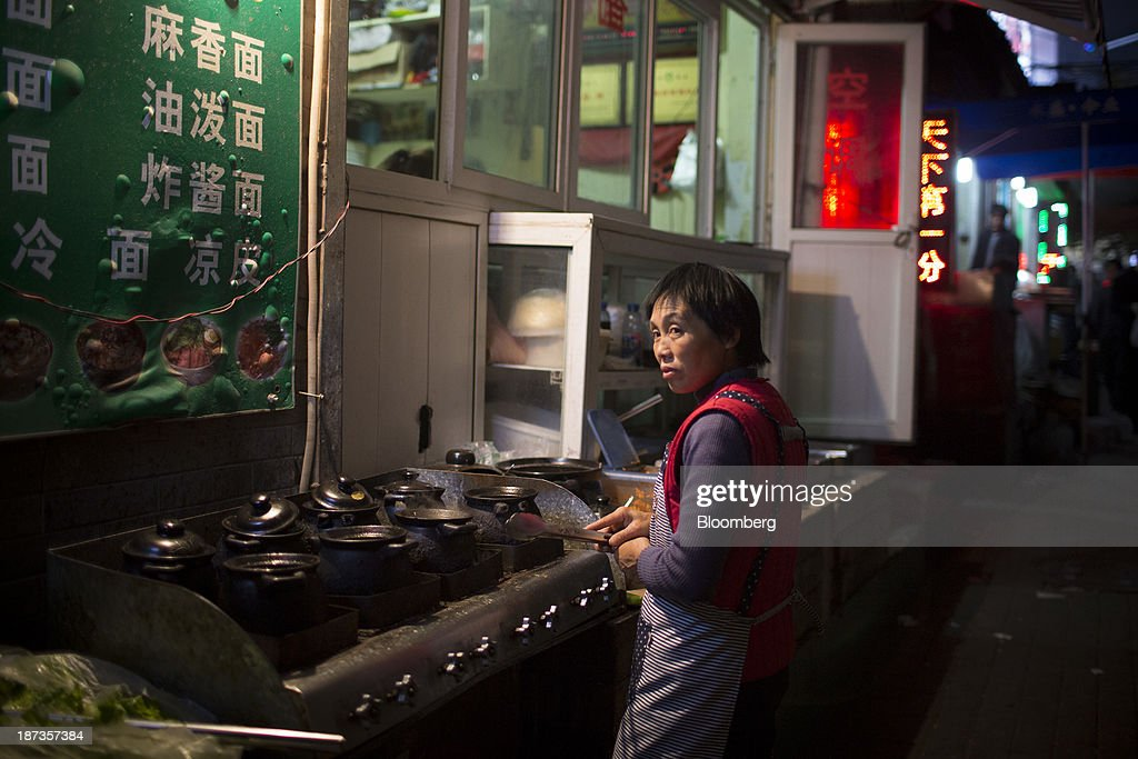 A woman prepares food on the street in Jinan, China, on Wednesday, Nov. 6, 2013. The third plenary session of the 18th Communist Party of China Central Committee will be held from Nov. 9 to Nov. 12 in Beijing. Photographer: Brent Lewin/Bloomberg via Getty Images