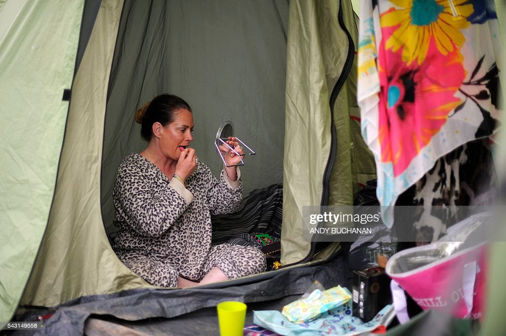 A woman prepares for the day on day five of the Glastonbury Festival of Music and Performing Arts on Worthy Farm near the village of Pilton in Somerset, South West England on June 26, 2016. / AFP / Andy Buchanan