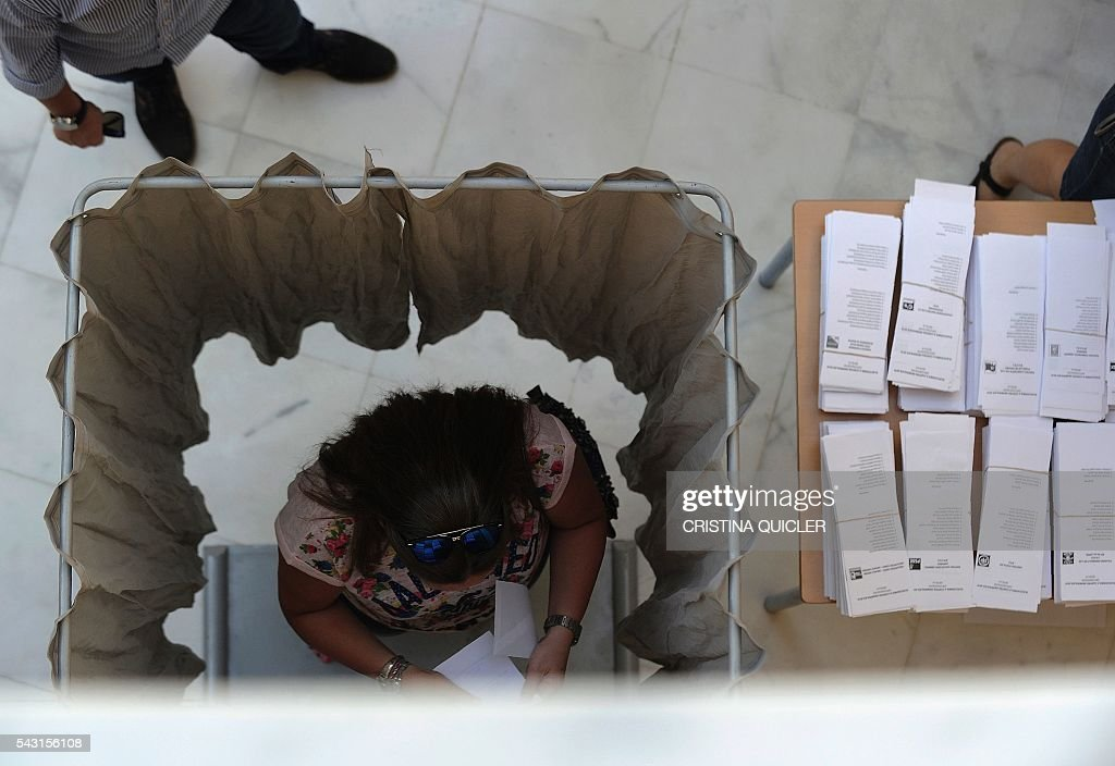 A woman prepares her ballot in a polling booth before casting her ballot for Spain's general election at the Casa Museo in Bollullos de la Mitacion, near Sevilla on June 26, 2016. Spain votes today, six months after an inconclusive election which saw parties unable to agree on a coalition government. / AFP / CRISTINA