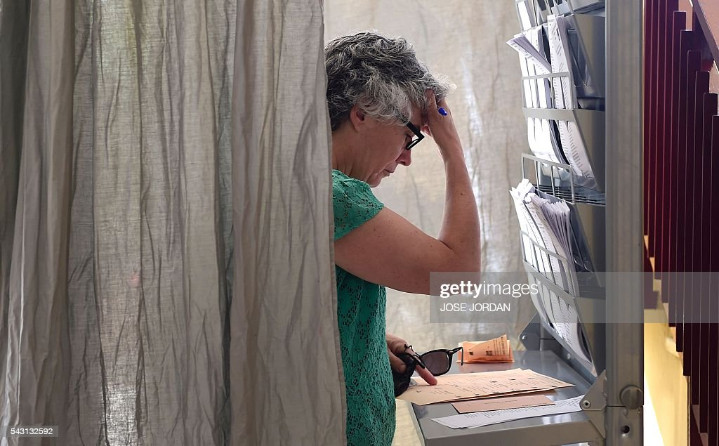 A woman prepares her ballot in a polling booth before voting in Spains general election at the Bernadette college polling station in Moncloa-Aravaca, Madrid, on June 26, 2016. Spain votes today, six months after an inconclusive election which saw parties unable to agree on a coalition government. JORDAN