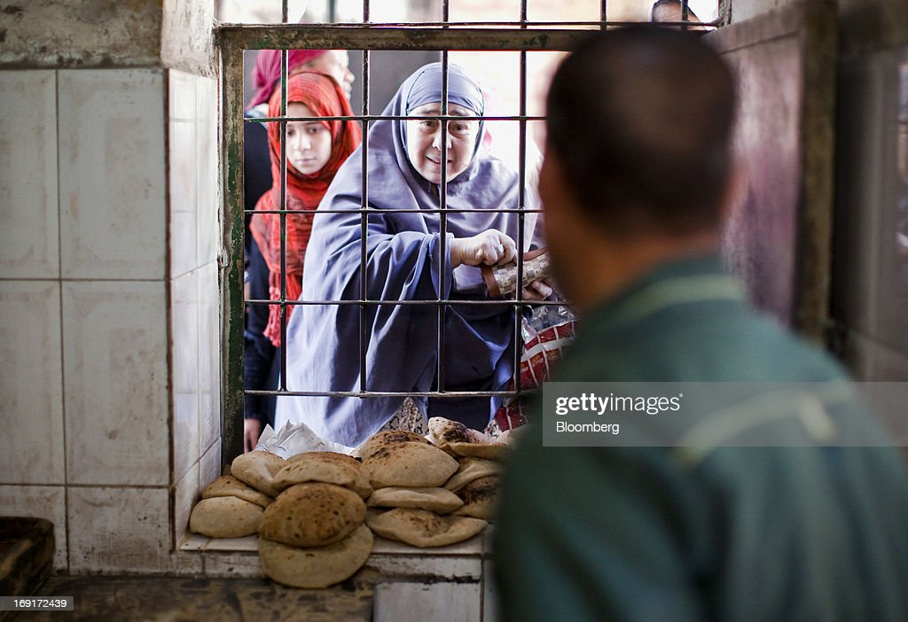 A woman prepares to buy bread from the window of a bakery in Cairo, Egypt, on Monday, May 20, 2013. Egypt will curb wheat imports by 31 percent to 8 million metric tons in 2012-13, still enough to make it the world's biggest buyer, the U.S. Department of Agriculture estimates. Photographer: Shawn Baldwin/Bloomberg via Getty Images