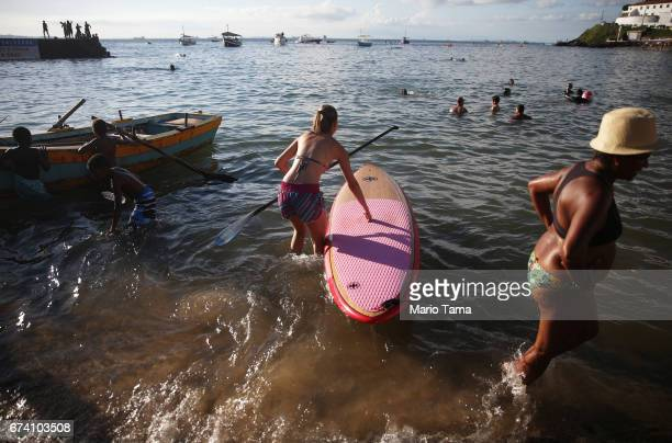 A woman prepares to paddle board as other gather in the Barra neighborhood in an upscale section of the city on April 19 2015 in Salvador Brazil