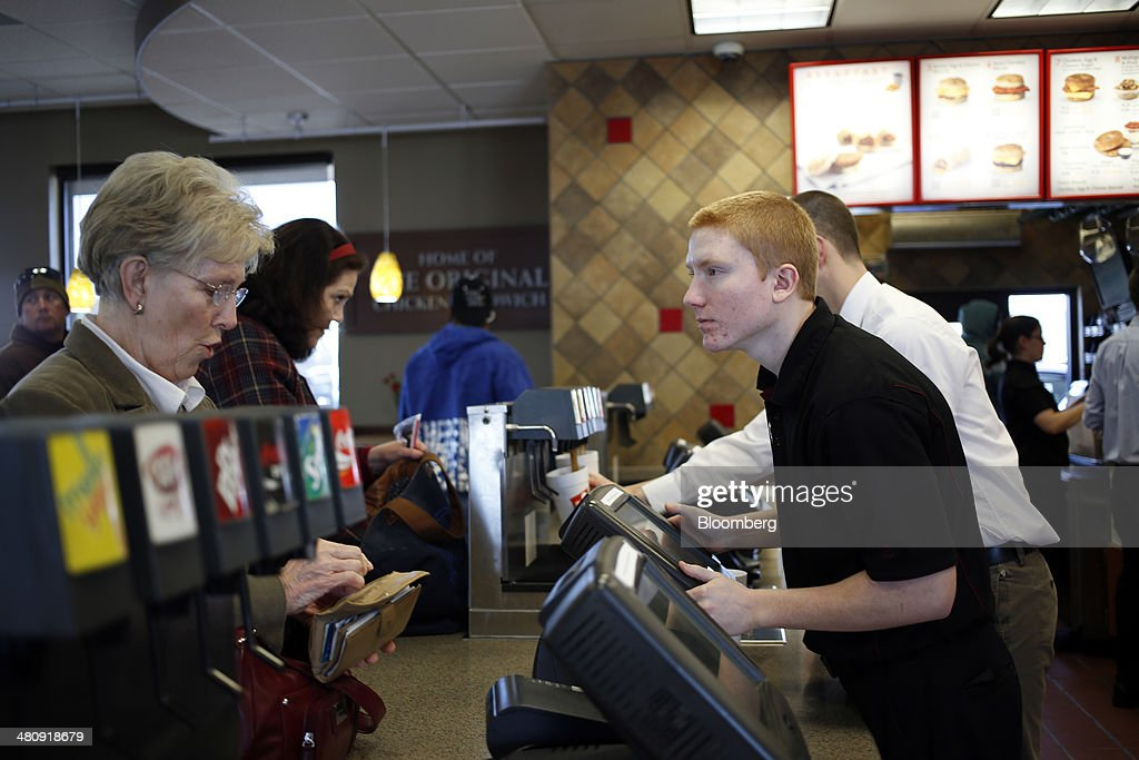 A woman prepares to pay for her order at a Chick-fil-A Inc. restaurant in Bowling Green, Kentucky, U.S., on Tuesday, Mar. 25, 2014. The U.S. economy grew more rapidly in the fourth quarter than previously estimated as consumer spending climbed by the most in three years, showing the expansion had momentum heading into this years harsh winter. Photographer: Luke Sharrett/Bloomberg via Getty Images