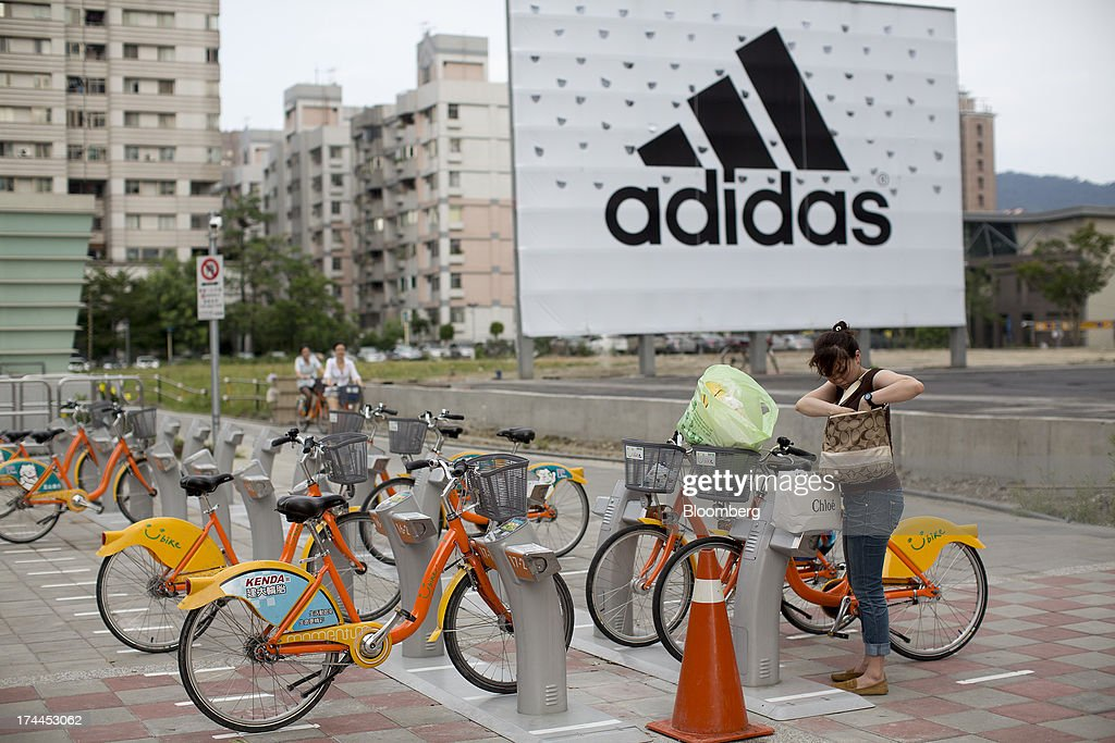 A woman prepares to rent a bicycle at a YouBike bicycle rental station in front of an Adidas AG advertisement on Hsin Yi Road in Taipei, Taiwan, on Wednesday, July 24, 2013. Taiwan President Ma Ying-jeou ruled out driving down the Taiwan dollar to boost exports following the currencys rally against the yen and said the government still aims for growth of at least 2 percent this year. Photographer: Jerome Favre/Bloomberg via Getty Images