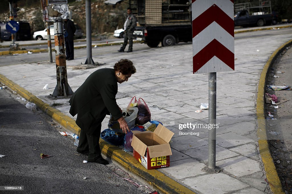 A woman prepares to transfer her goods from carrier bags into a cardboard box after visiting the 'Bazaar of Schisto' open market in Piraeus, Greece, on Sunday, Nov. 18, 2012. European finance ministers aim to stitch together Greece's next aid payment as a sputtering euro-area economy and a spat with the International Monetary Fund cloud efforts to resolve the debt crisis. Photographer: Kostas Tsironis/Bloomberg via Getty Images