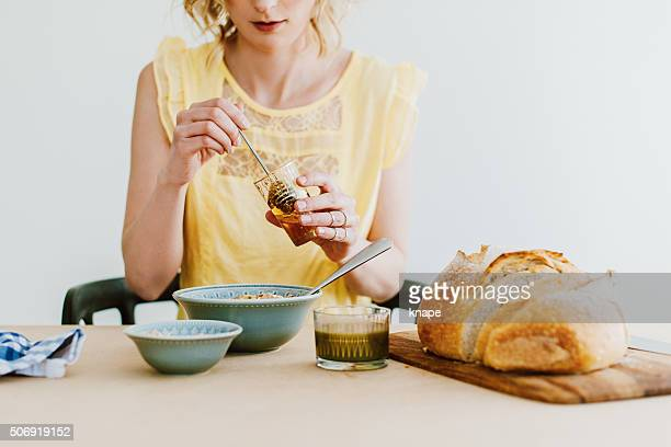 Woman preparing breakfast yogurt and cereals