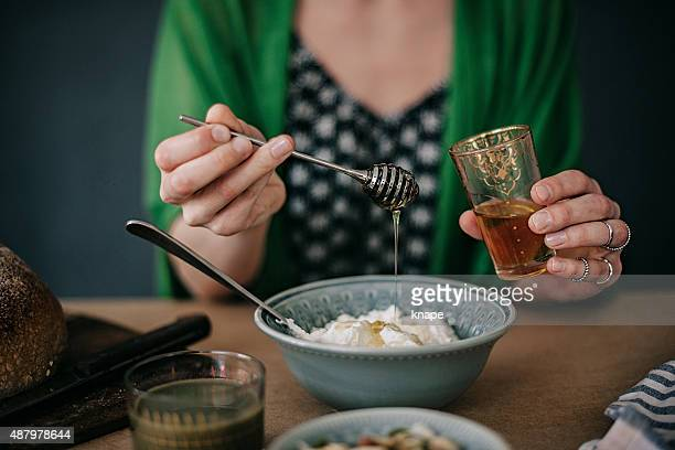 Woman preparing breakfast yogurt and honey