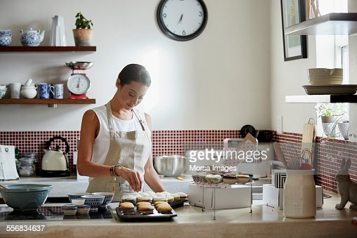 Woman preparing cupcakes in kitchen