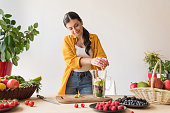 portrait of young woman preparing detox drink at home