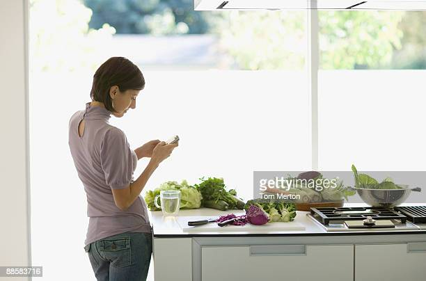 Woman preparing food and text messaging in kitchen