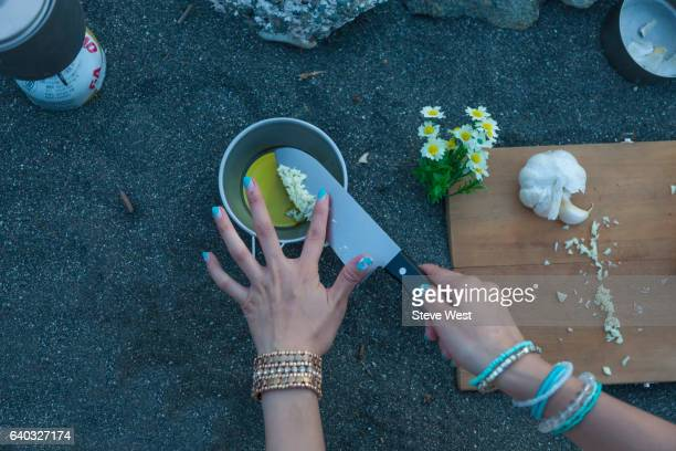 Woman Preparing Food With Camping Equipment On The Beach