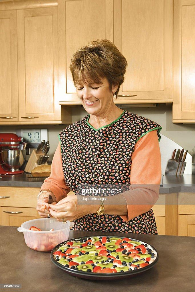 Woman preparing fruit dessert in kitchen : Stock Photo