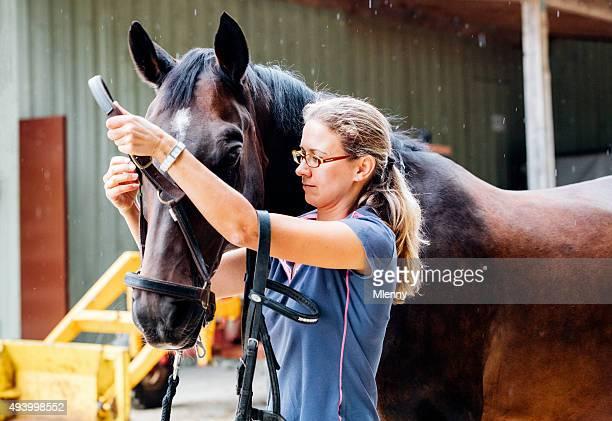 Femme préparant Accessoires textiles et harnais de cheval pour une balade à cheval