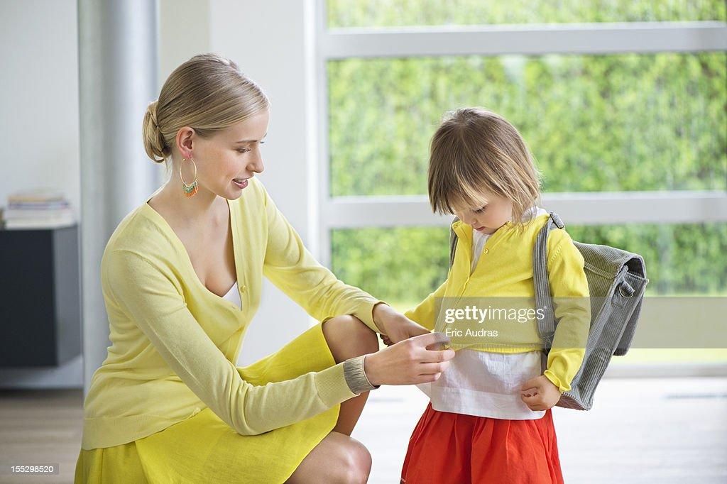 Woman preparing her daughter for school