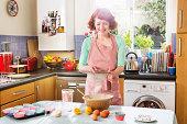Woman preparing making cakedough in kitchen.