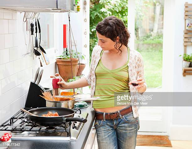 Woman preparing meal in kitchen.