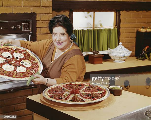 Woman preparing pizza in kitchen, portrait