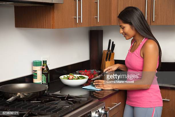Woman preparing salad in kitchen