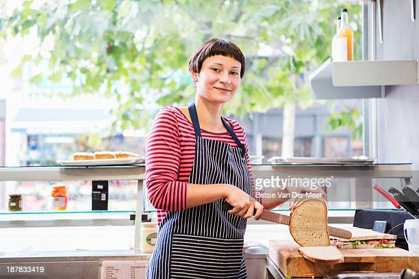 Woman preparing sandwiches in deli shop.