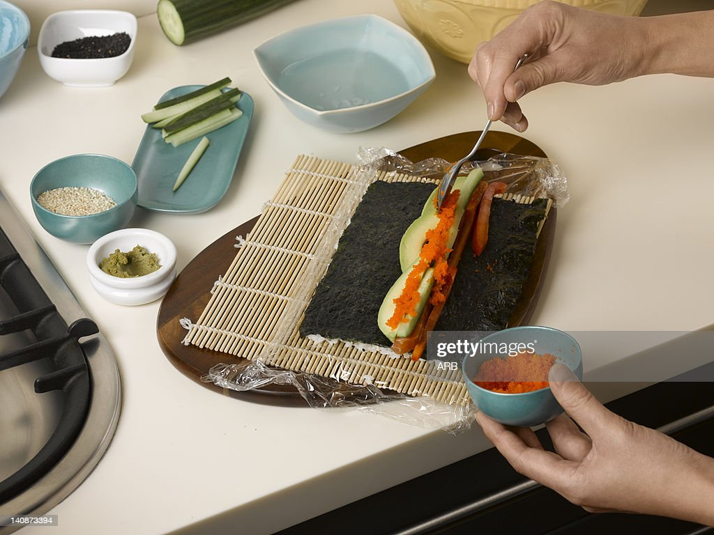 Woman preparing sushi roll at table : Stock Photo