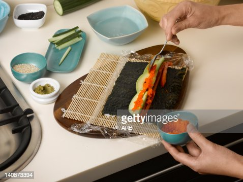 Woman preparing sushi roll at table : Stock Photo
