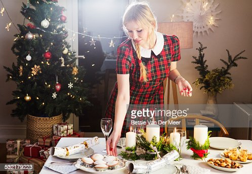 Woman preparing table with food for Christmas.
