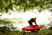 Woman preparing to enter river in kayak
