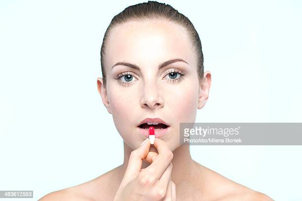 Woman preparing to take capsule