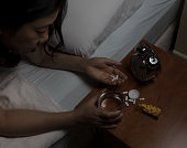 Woman picking up pain killer pills on night stand. Depression and addiction concept. Select focus on hand and pills.