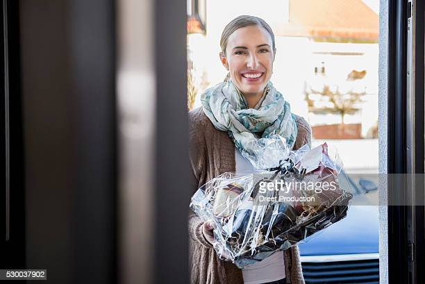 Woman presented with a gift to the front door of a friend, Munich, Bavaria, Germany