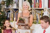 Woman presenting a Christmas pudding