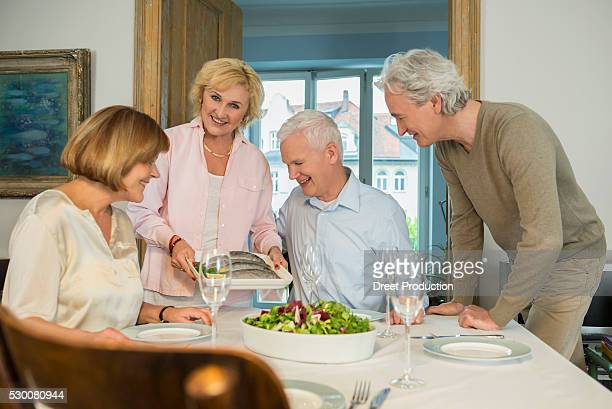 Woman presenting trout fish to her friends, smiling