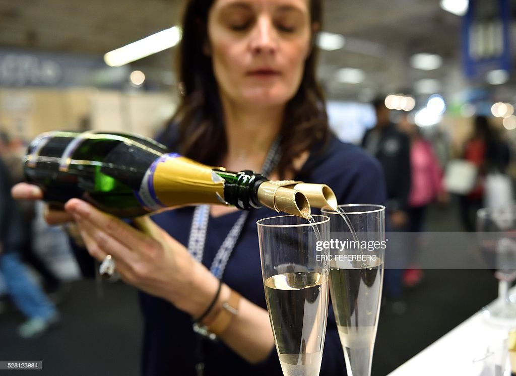 A woman presents a double pouring spout at a stand of the 'Concours Lepine' (Lepine contest) at Paris' fair, on May 4, 2016 in Paris. The Lepine contest, a competition for inventors in the world, was launched in 1901 by Louis Lepine, the city's police chief and has chalked up some notable successes, such as the world's first artificial heart in 1937. / AFP / ERIC