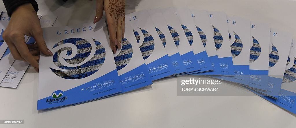 A woman presents travel brochures at the booth of Greece at the Internationale Tourismus Boerse in Berlin March 5 2015 More than 10000 exhibitors...