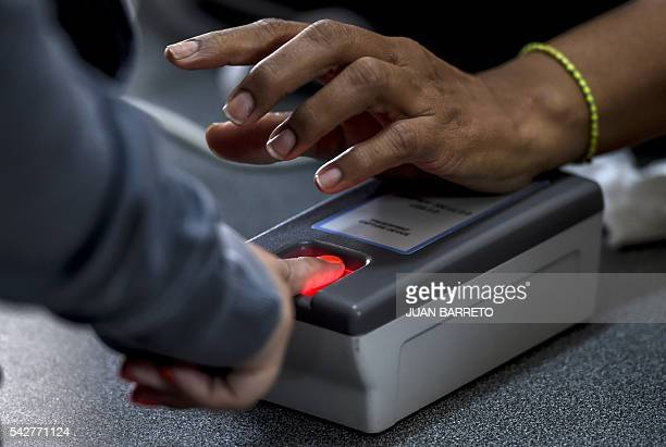 A woman presses a finger on a fingerprint scanner during the authentication procedure of her signature for a recall referendum before the National...