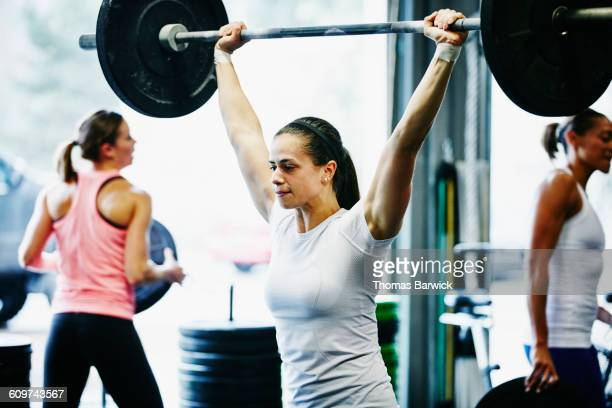 Woman pressing barbell overhead during workout