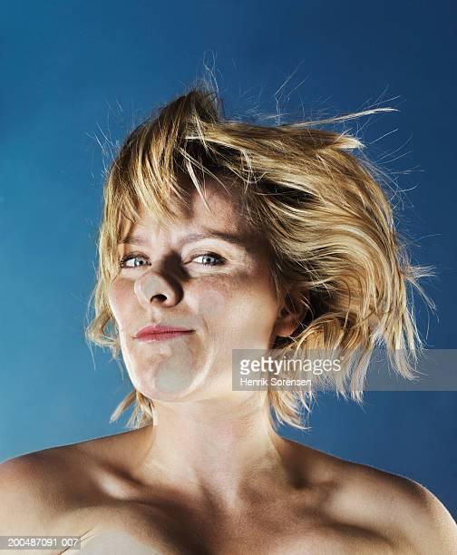 Woman pressing face against glass pane, portrait