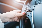 Closeup photo of woman pressing green phone control button on car steering wheel