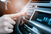 Closeup photo of woman pressing phone control button on car media system