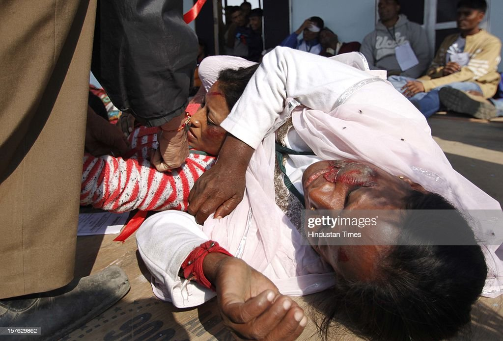 A woman pretending to be dead during a mock drill session at Burari ground on December 4,2102 in New Delhi, India. Mock Drill performs at various place in the capital to test the alertness and responds during the time of emergency situation such as Earthquake, Fire, Bomb Blast.