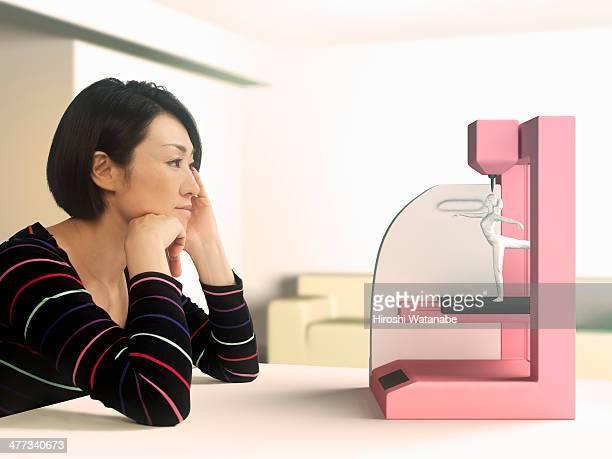 Woman prints a figure by 3D printing
