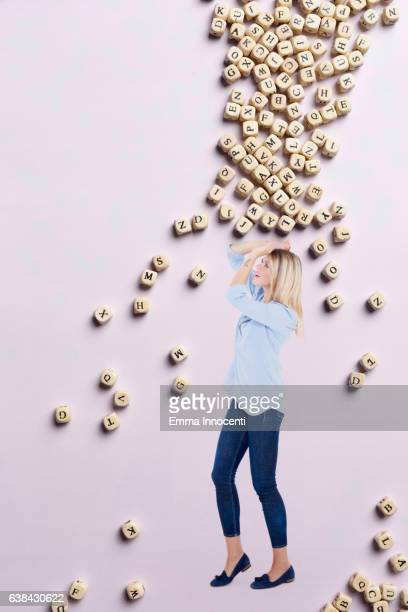 Woman protecting herself from falling letters