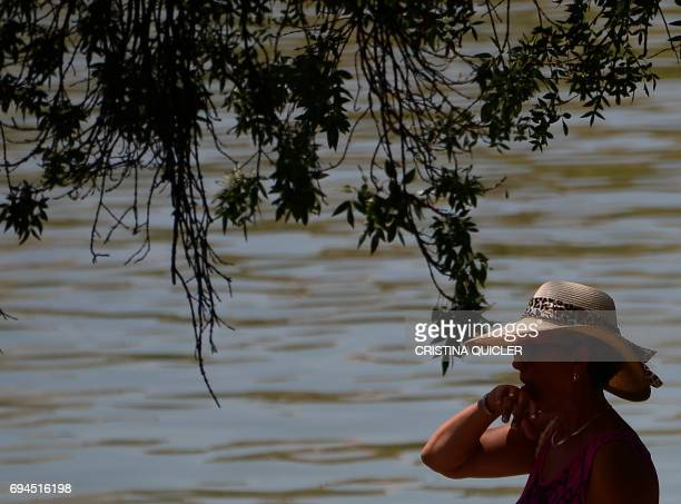 A woman protects herself from the sun under a hat near the Guadalquivir river in Sevilla on June 10 2017 QUICLER