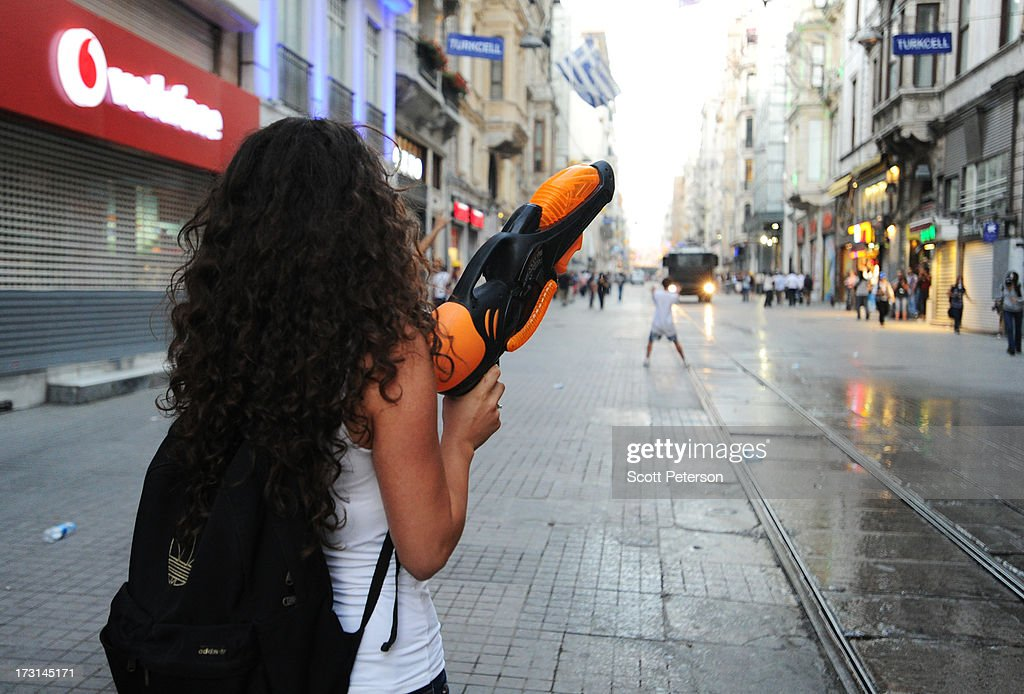 A woman protestor holds a large squirt gun to parody water cannons used by police, as Turkish riot police battle anti-government protestors along the Istiklal shopping street near Taksim Square on July 8, 2013 in Istanbul, Turkey. The protests began in late May over the Gezi Park redevelopment project and saving the park trees adjacent to Taksim Square but swiftly turned into a protest aimed at Prime Minister Recep Tayyip Erdogan and what protestors call his increasingly authoritarian rule. The protest spread to dozens of cities in Turkey, in secular anger against Mr. Erdogan and his Islam-rooted Justice and Development Party (AKP).