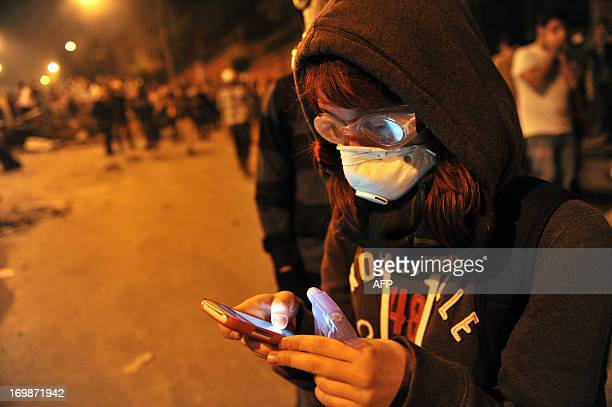 A woman protestor uses mobile phone to report the latest news about the clashes near Taksim in Istanbul on June 3 2013 during a demonstration against...